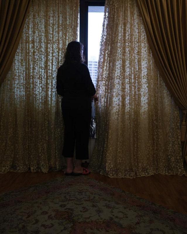 نیوشا توکلیان. مادر عکاس در کنار پنجرهی اتاقش به شکوفهی درخت باغچه نگاه میکند. توکلیان نوشته: «این او را حداقل برای لحظهای خوشحال میکند.»