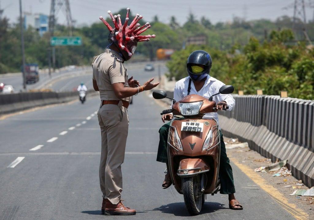P. Ravikumar از رویترز. افسر پلیسی با نام راجش بابو که کلاهی بهشکل ویروس کرونا به سر گذاشته، از موتورسوار میخواهد که طی قرنطینهی 21 روزهی سرتاسری در هند در خانه بماند تا از شیوع این ویروس جلوگیری شود. چنای، هند، 28 مارس 2020