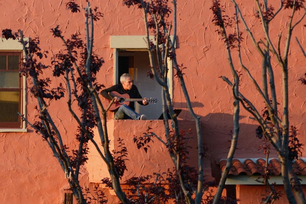 Kate Munsch از رویترز. دنی ورتایمر در حال گیتار زدن و خواندن برای همسایههایش از بالکن خانهاش در اُکلند کلیفرنیا، دو روز بعد از اجرای «دستور ایالتی ماندن در خانه» از سوی فرماندار کلیفرنیا. 21 مارس 2020