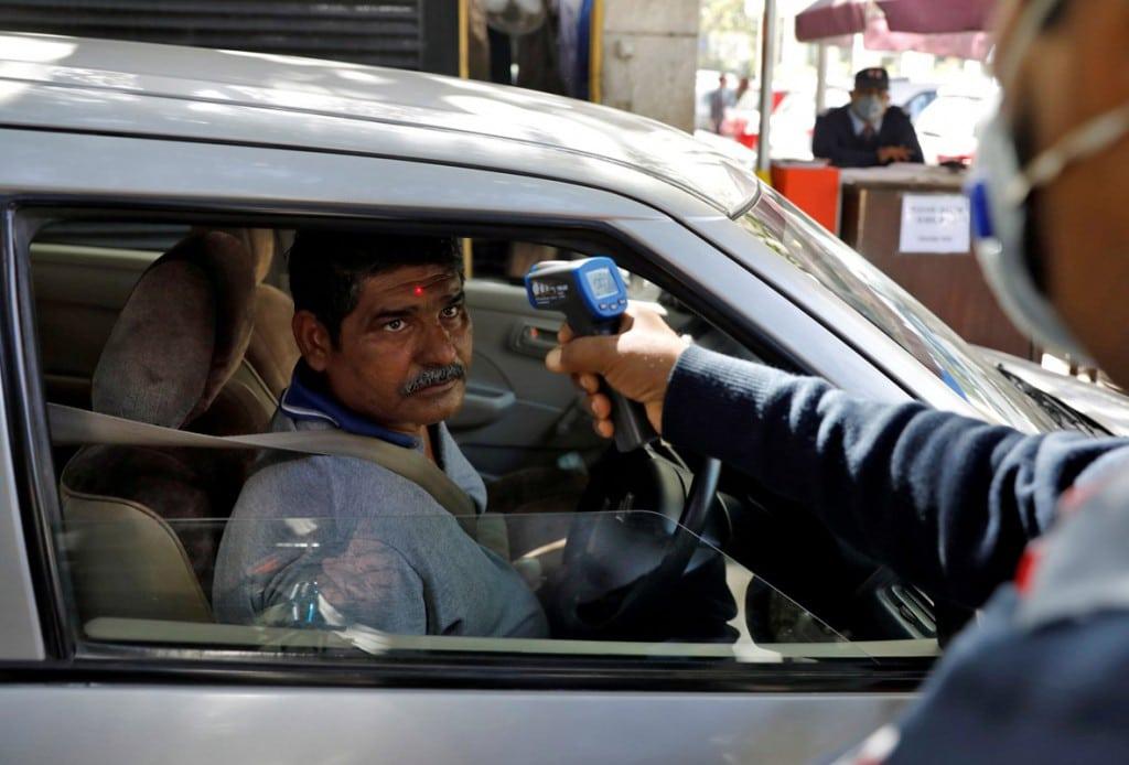 Adnan Abidi از رویترز. نیروی امنیتی با دماسنج مادون قرمز دمای بدن مردی را هنگام ورود به ادارهای در دهلینو، هند اندازهگیری میکند. 9 مارس 2020