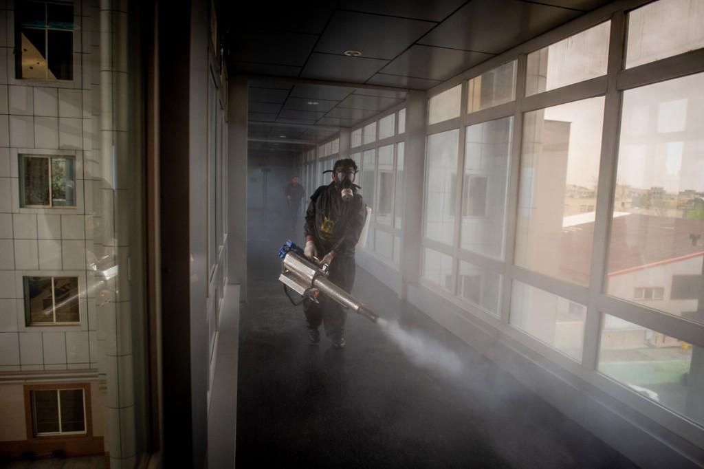 علی محمدی از بلومبرگ. یک آتشنشان در حال ضدعفونی کردن ساختمانی در تهران در دوران شیوع ویروس کرونا. 18 مارس 2020
