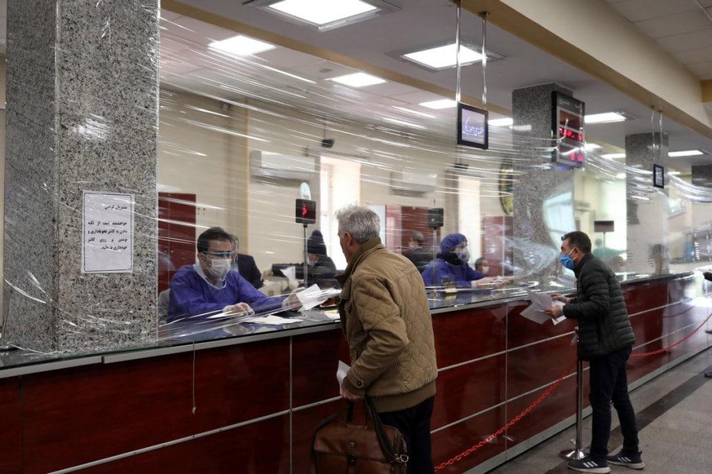 علی خارا از آژانس خبری غرب آسیا (WANA). طی دوران شیوع ویروس کرونا پوششی پلاستیکی میان کارمندان یک بانک در تهران و مشتریانش کشیده شده است. 17 مارس 2020