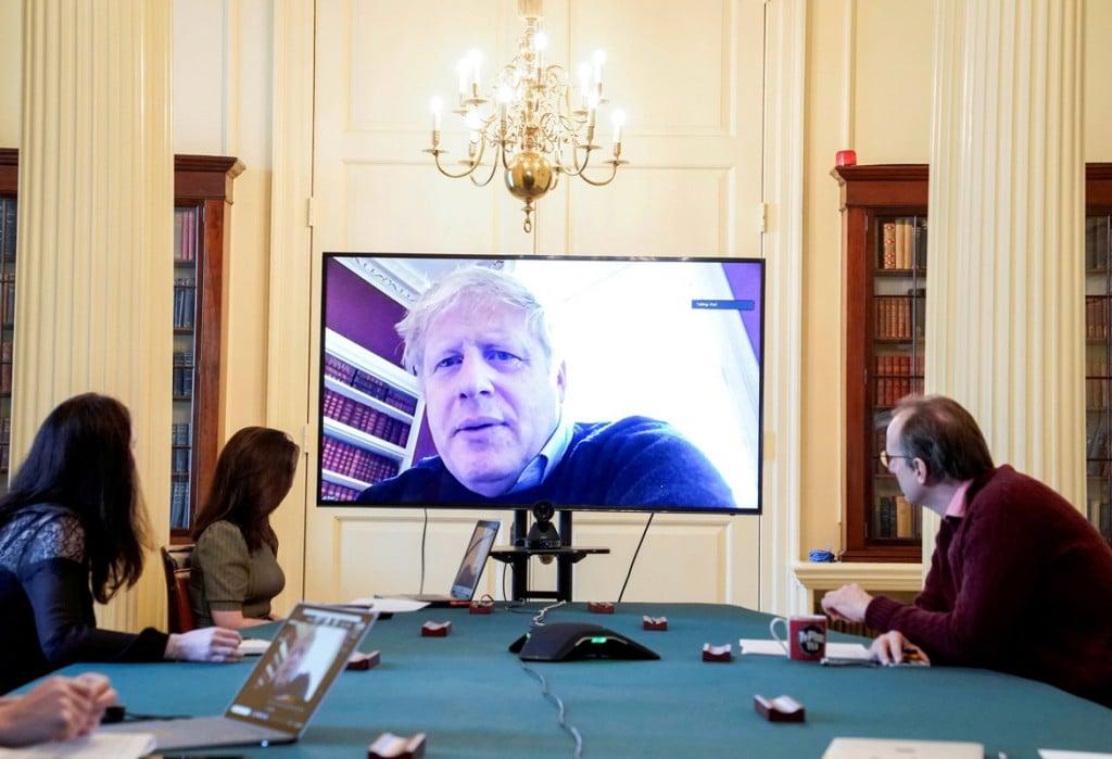 Andrew Parsons از 10 Downing Street و Handout. نخست وزیر بریتانیا بوریس جانسون از طریق یک نمایشگر جلسهی دولت دربارهی ویروس کرونا را برگزار میکند. او پس از آن که مشخص شد به ویروس کرونا مبتلا است خود را قرنطینه کرده است. لندن، 28 مارس 2020