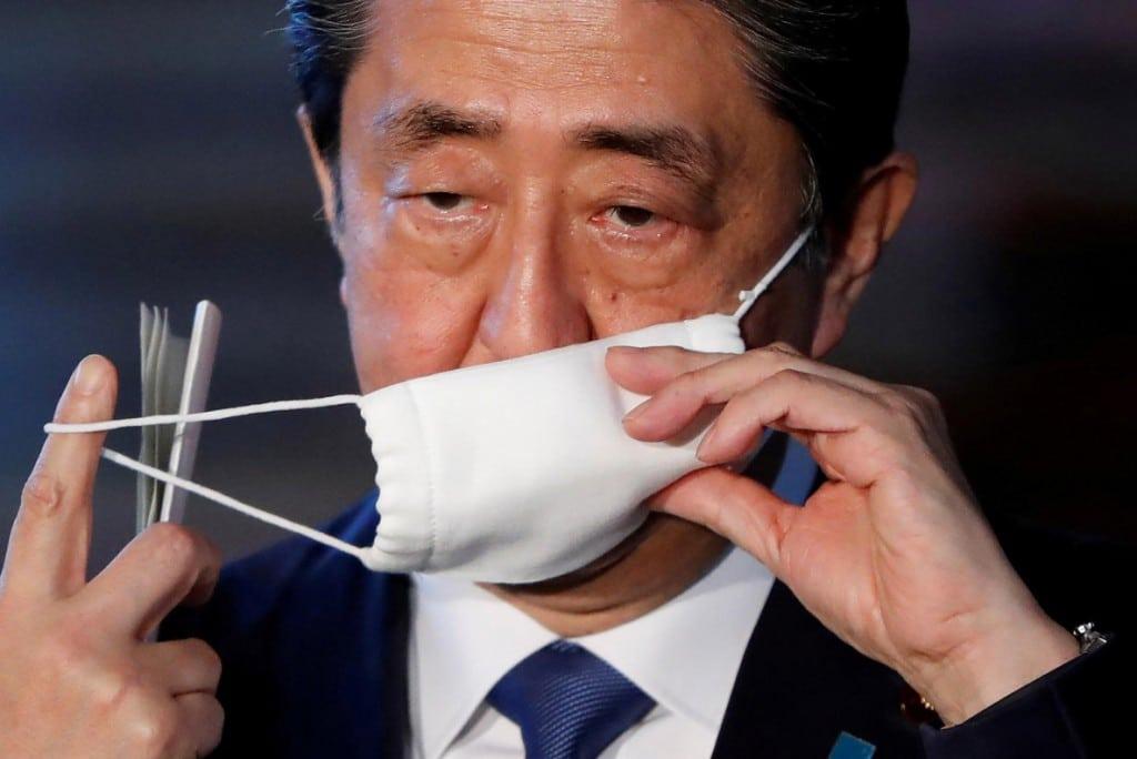 Issei Kato از رویترز. نخستوزیر ژاپن شینزو آبه در حال برداشتن ماسک از روی صورتش بههنگام رسیدن به محل سخنرانی مطبوعاتی دربارهی واکنش ژاپن به شیوع ویروس کرونا در توکیو. ژاپن طی این مدت با چالش تعویق زمان برگزاری بازیهای المپیک 2020 روبهرو بوده است.