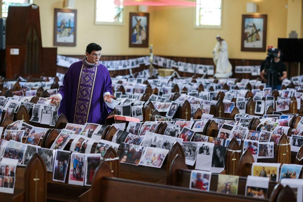 Rodolfo Buhrer از رویترز. کشیش کاتولیک رجینالدو مانزوتی در کنار عکسهایی از دینداران در کلیسایی در کوریتیبا، برزیل در حال اجرای برنامهی زنده تلویزیونی. 21 مارس 2020