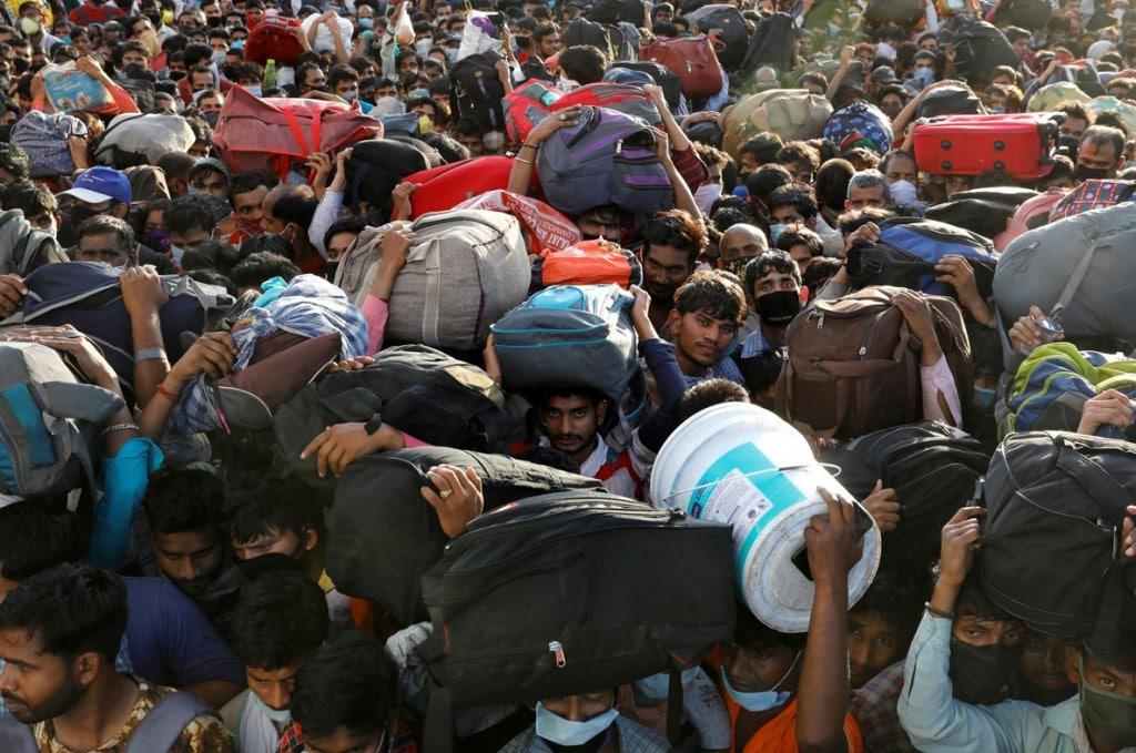 Anushree Fadnavis از رویترز. جمعیت کارگران مهاجر در بیرون ترمینالی در قاضیآباد در اطراف دهلینو منتظر اتوبوس هستند تا طی قرنطینهی 21 روزهی سرتاسری در هند به روستاهاشان برگردند. 28 مارس 2020