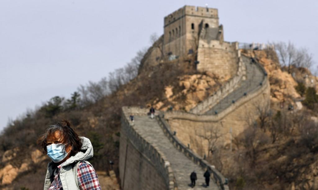 Andy Wong از اسوشیتدپرس. بازدیدکنندهای با ماسک روی صورت روی دیوار بزرگ چین. چین منشأ شیوع ویروس کرونا در جهان بوده است.