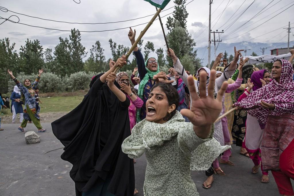 Dar Yasin. زنان در حال شعار دادن در زمانی که پلیس هند با پرتاب گاز اشکآور و شلیک هوایی تلاش دارد از شکلگیری تجمع اعتراضی در سرینگر کشمیر جلوگیری کند، 18 مرداد 1398