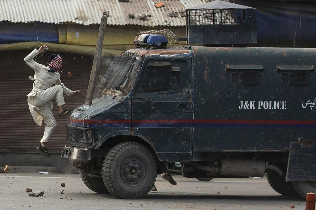 Dar Yasin. یک معترض کشمیری در حال پریدن روی کاپوت یک ماشین زرهپوش هندی و پرتاب سنگ به سمت آن، طی اعتراضات سرینگر، کشمیر، 10 خرداد 1398