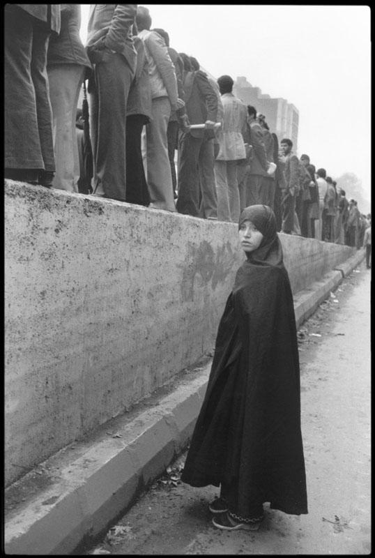 عباس عطار. زنی در تظاهرات ضد شاه پشت مردان ایستاده، تهران، 1978