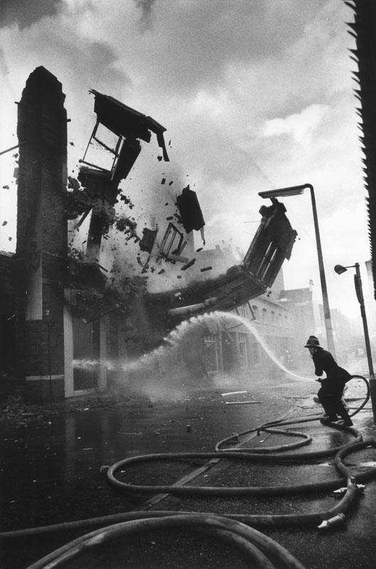 عباس عطار. آتشنشان در لحظهی انفجار ساختمان با بمبی که احتمالاً ارتش جمهوری ایرلند شلیک کرده، ایرلند شمالی، بلفاست، 1972