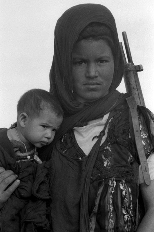 کریستین اشپنگلر. زنی بههمراه تفنگ کودکش را در آغوش گرفته، طی تمرین نظامی برای نبرد علیه اشغال مراکش و موریتانی، دسامبر 1976