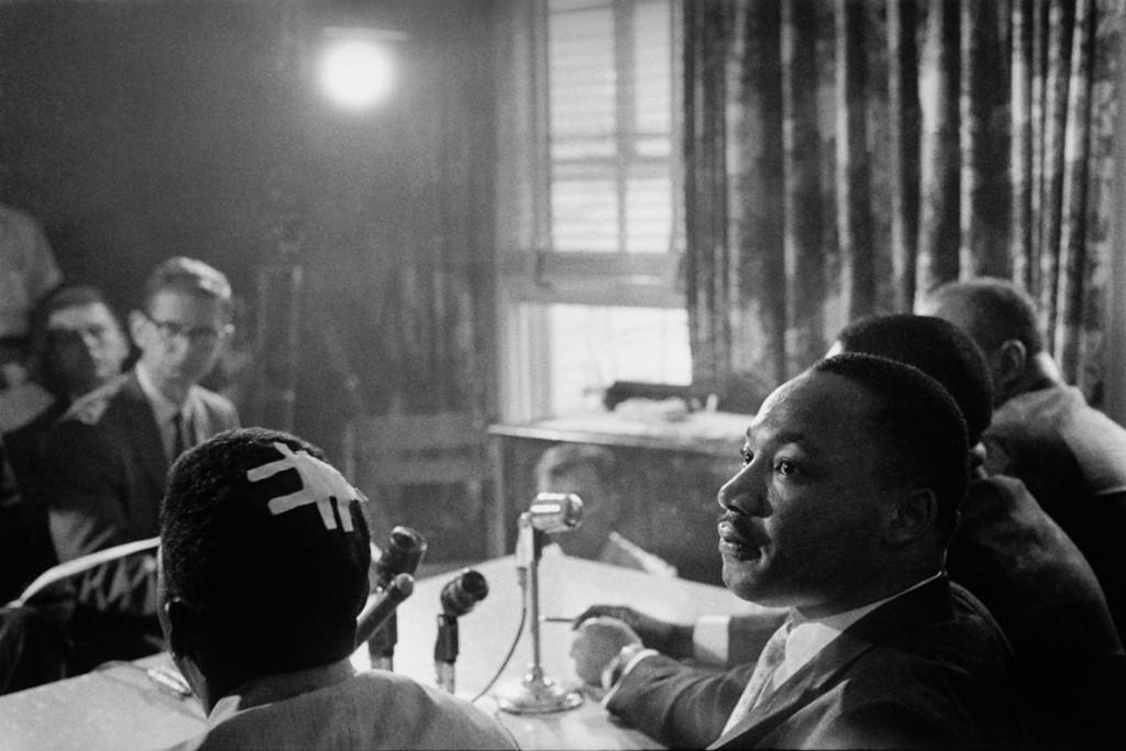 بروس دیویدسن. مارتین لوترکینگ در کنفرانس مطبوعاتی اعلام میکند که کار رانندگان آزادی ادامه خواهد یافت. جان لوییس (فرد کناری کینگ که سرش بانداژ شده) کمی قبل مورد حملهی گروه کوکلاکسکلن قرار گرفته بود، آمریکا، 1961