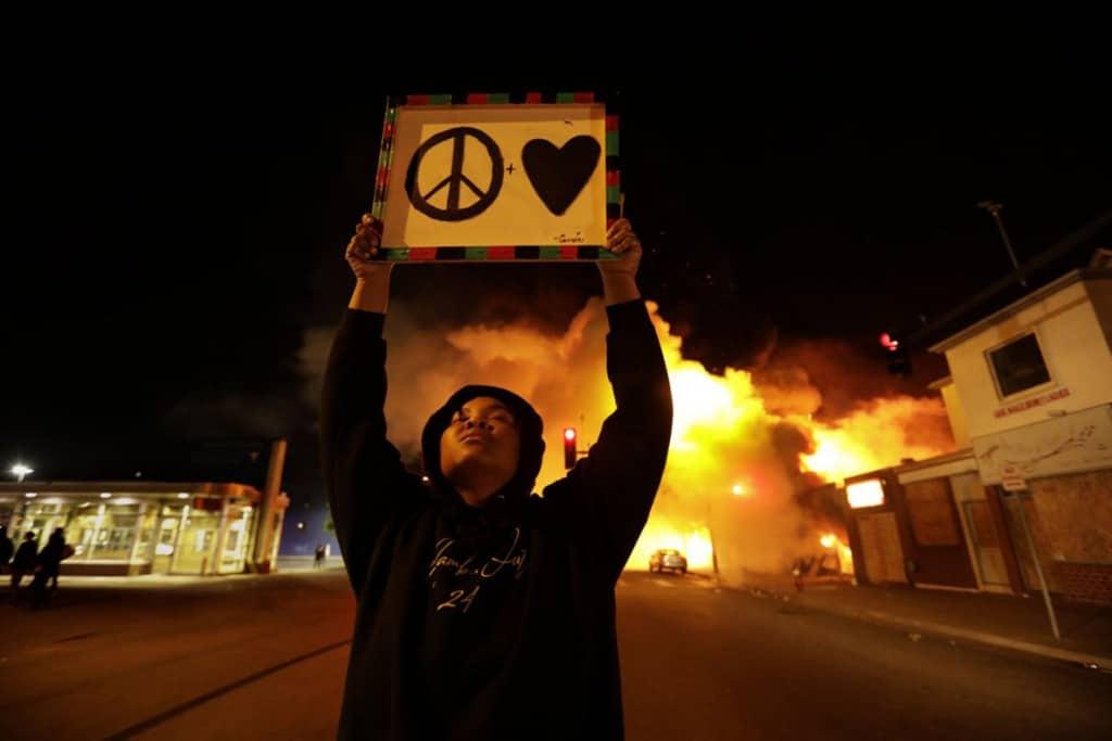Carolyn Cole از لسآنجلس تایمز. زنی در حال فراخواندن دیگران به صلح و عشق، در حالی که علیرغم دستور منع رفتوآمد، اعتراضات و غارت در سرتاسر شب ادامه داشته، مینیاپلیس، مینسوتا، 29 می 2020
