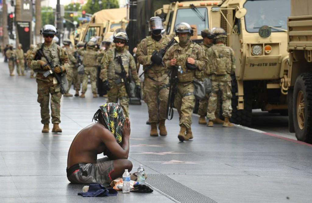 Wally Skalij از لسآنجلس تایمز. بندو کِو روی زمین نشسته و در حال دعاست در حالی که گارد ملی در حال آمدن هستند. بلوار هالیوود، لسآنجلس، کلیفرنیا، 2 ژوئن