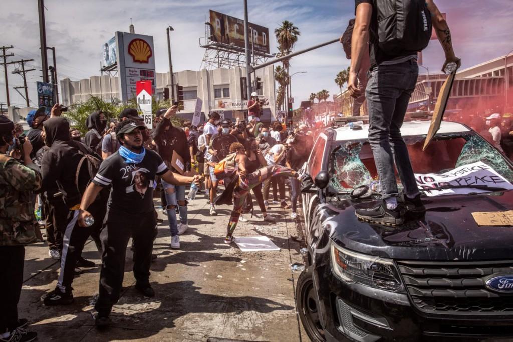 Bryan Denton از نیویورک تایمز. معترضان در کنار ماشین گشت پلیس رهاشده در زمانی که اعتراضات به خشونت کشیده شد. لسآنجلس، کلیفرنیا، 30 می 2020