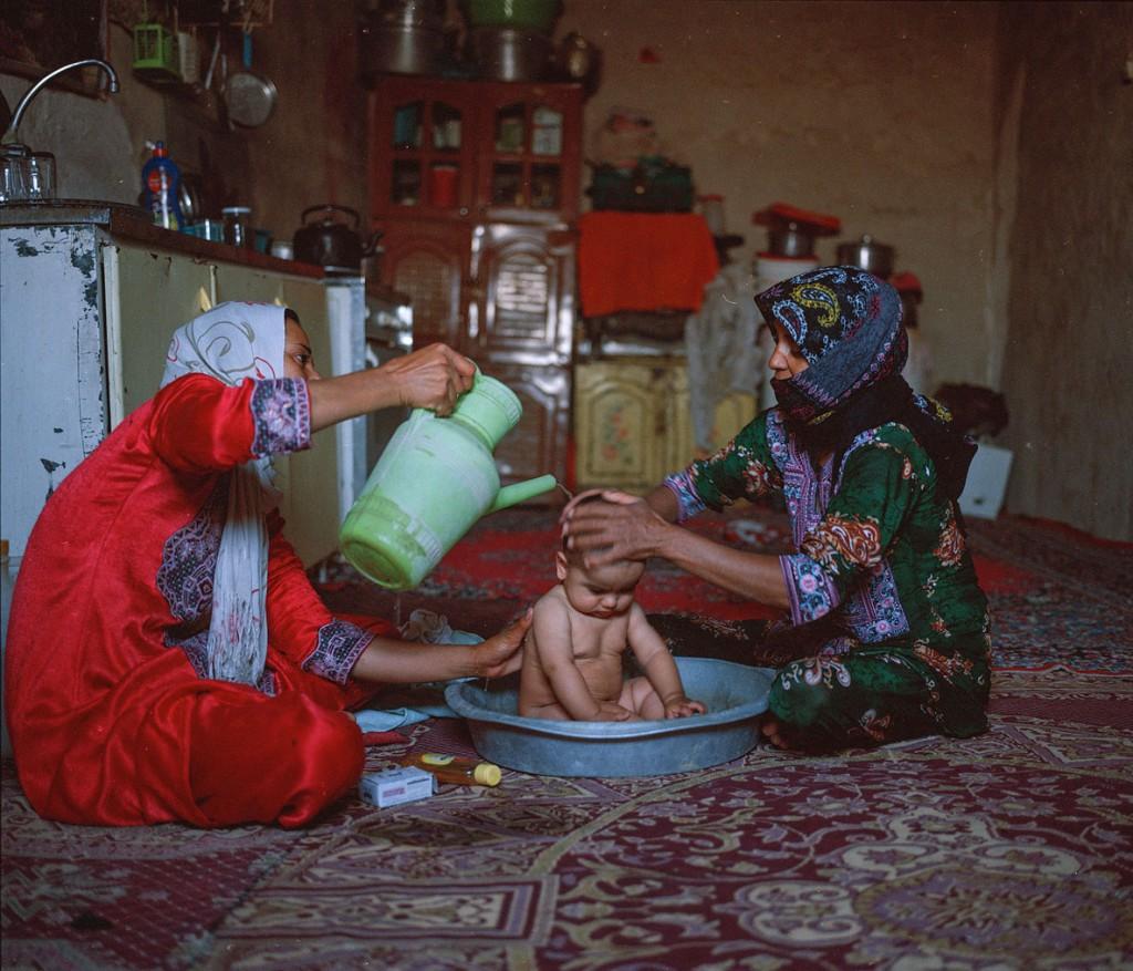 هاشم شاکری. از مجموعهی Elegy for the Death of Hamun زنان روستای ریگ موری در حال شستوشوی یک کودک. در این روستا آب آشامیدنی تنها از 8 صبح تا 3 بعدازظهر در دسترس است.