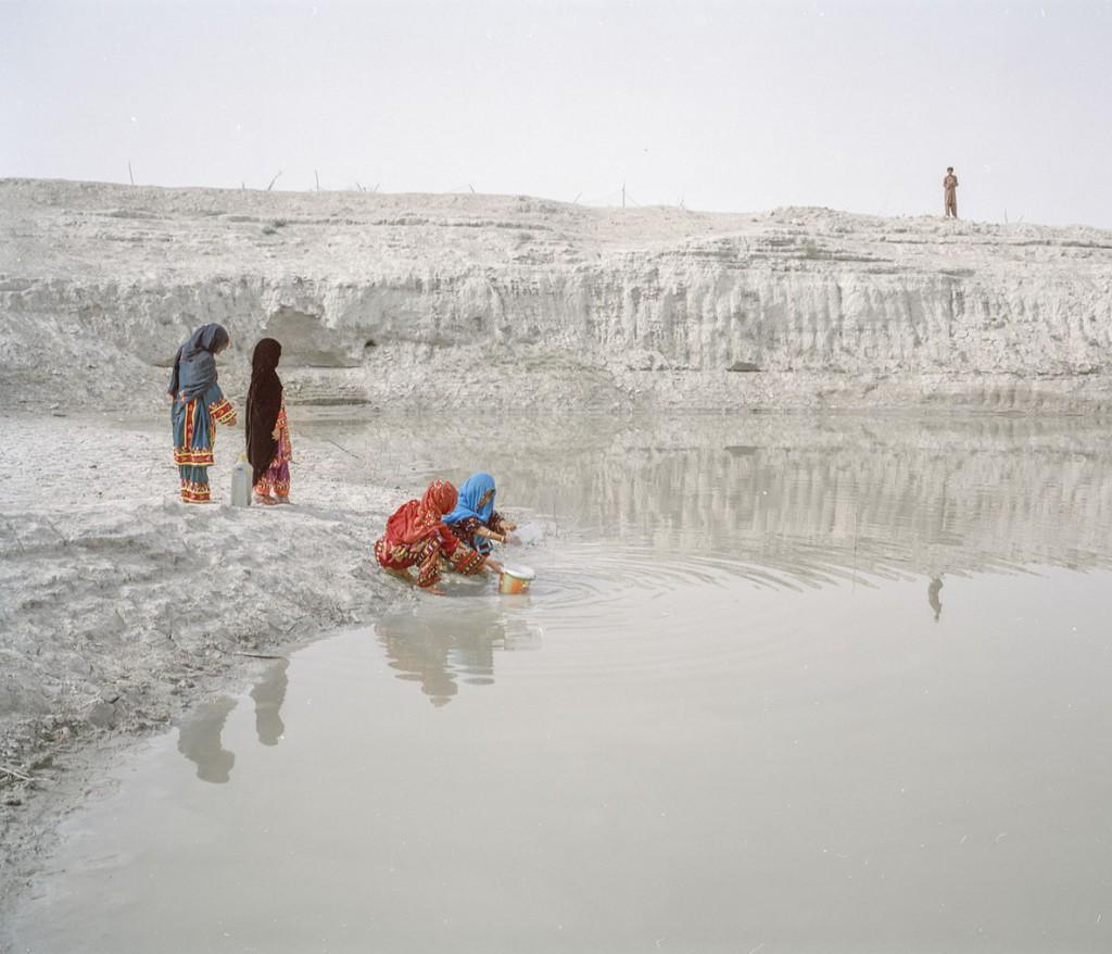 هاشم شاکری. از مجموعهی Elegy for the Death of Hamun چهار دختر از یک خانواده در روستای چوتانی در حال جمع کردن آب از «هوتاگ» (چالهای که آب باران در آن جمع میشود). طی دوران خشکسالی، این چالهها کثیف و گلآلود میشوند، با این حال آنها تنها منبع آب در دسترس بسیاری از مردم هستند. آنها چارهای جز این ندارند که این آبها را بجوشانند و بنوشند.
