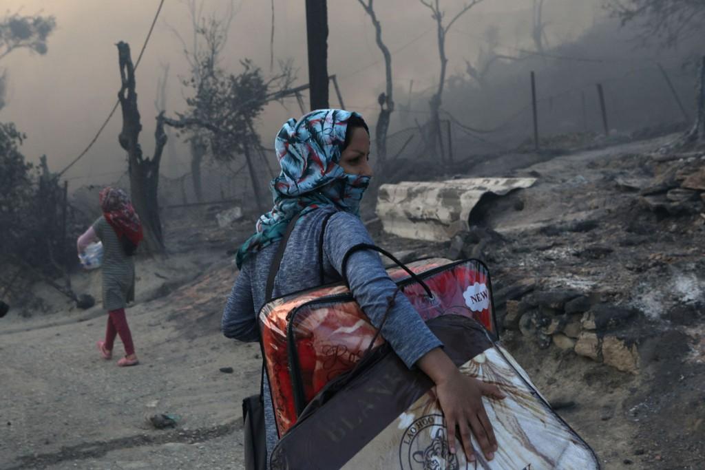 Elias Marcou از رویترز. یک زن مهاجر در حال حمل داشتههایش پس از آتشسوزی کمپ موریا، محل نگهداری پناهجویان و مهاجران در جزیره لسبوس یونان، 9 سپتامبر 2020
