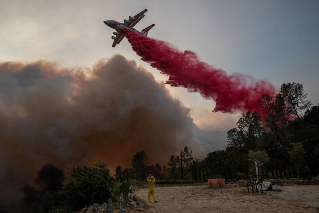 Adrees Latif از رویترز. زنی در لباس ضدحریق در حال عکاسی کردن از هواپیمایی که در حال پاشیدن ماده ضدحریق قرمزرنگ روی آتش است، طی آتشسوزی Glass Fire در دیر پارک، کلیفرنیا، آمریکا، 27 سپتامبر 2020