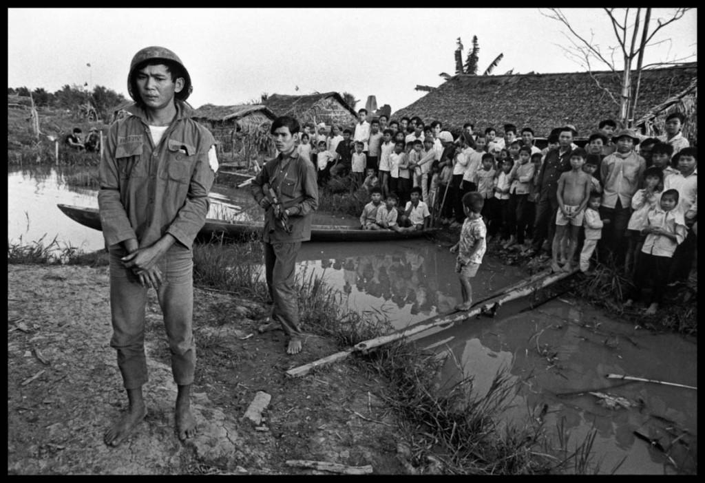 عباس عطار. سرباز ارتش ویتنام جنوبی از سوی ویتکُنگها (چریکهای کمونیست) به اسارت گرفته شده و در روستایی در معرض تماشای مردم قرار داده شده است، ویتنام، منطقهی دلتای جنوبی، 1973