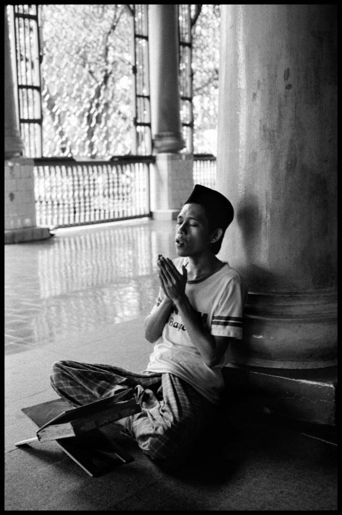 عباس عطار. مردی جوان در حال پرستش الله دستانش را بهشکل نیایش هندوها درآورده. بسیاری از نشانههای آیین هندو در مسلمانان اندونزی باقی ماندهاند، سوماترا، اندونزی، 1989