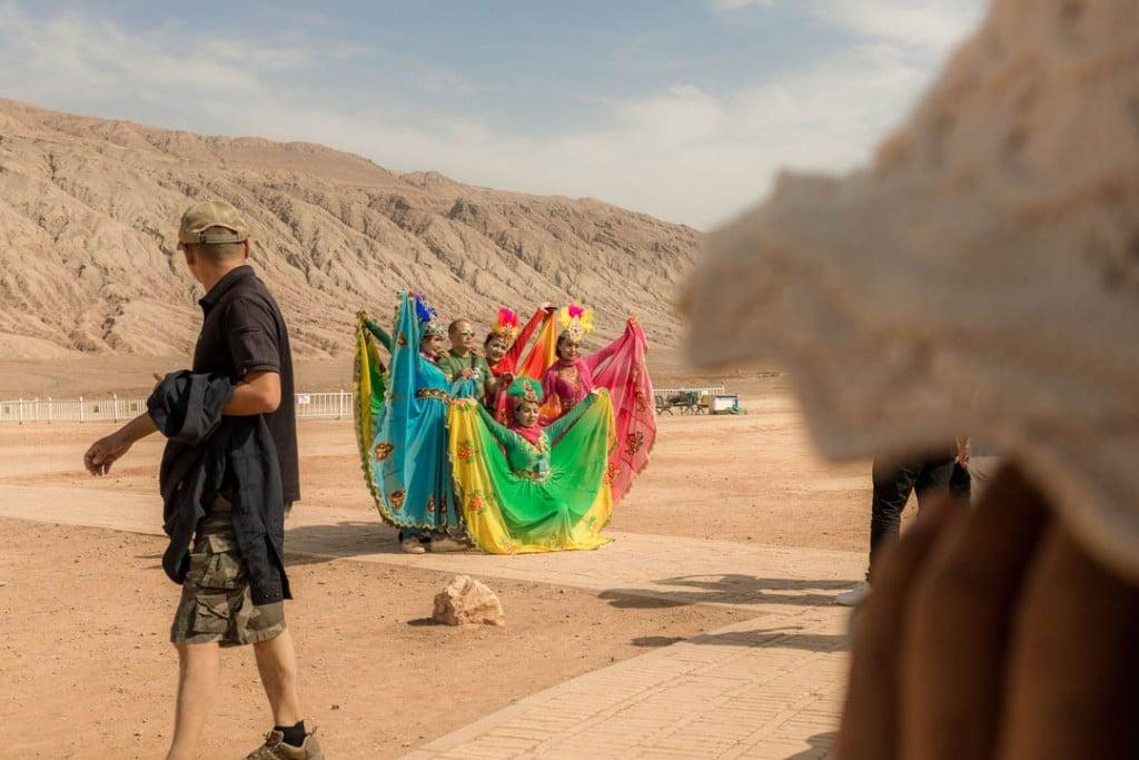 پاتریک وک. مرکز گردشگری حوالی تۇرپان معمولاً مقصد چینیهای نژاد هان است. دختران جوان اویغور لباسهای محلی پرزرقوبرق به تن میکنند و برای کسب درآمد با توریستهای چینی عکس میگیرند، استان سینکیانگ، 27 سپتامبر 2019
