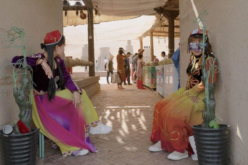 پاتریک وک. پارک صحرایی توریستی که معمولاً مقصد چینیهای نژاد هان است. دختران جوان اویغور با لباسهای محلی پرزرقوبرق برای کسب درآمد با توریستهای چینی عکس میگیرند، استان سینکیانگ، 28 سپتامبر 2019