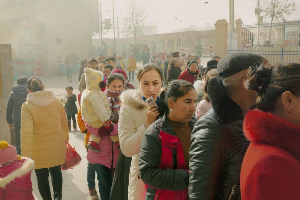 پاتریک وک. محلیهای اقلیت اویغور در صف منتظر بررسی کارت شناسایی و بازرسی بدنی پیش از ورود به بازار محلی، شهر خوتەن، استان سینکیانگ، 3 فوریه 2019