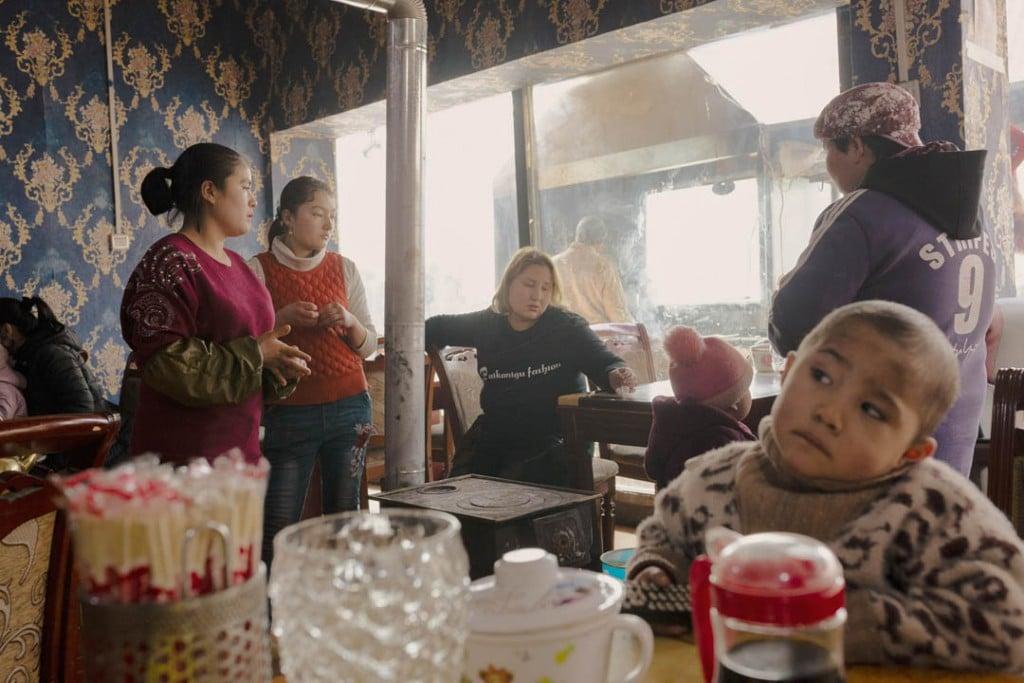 پاتریک وک. کارکنان رستوران و مشتریها بههمراه فرزندانشان در یک رستوران اویغوری در شهر باستانی خوتەن، استان سینکیانگ، 3 فوریه 2019