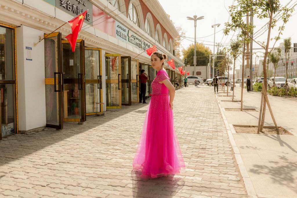پاتریک وک. دختر جوان اویغور در لباس مجلسی در خیابان شهر ئۈرۈمچى، استان سینکیانگ، 25 سپتامبر 2019