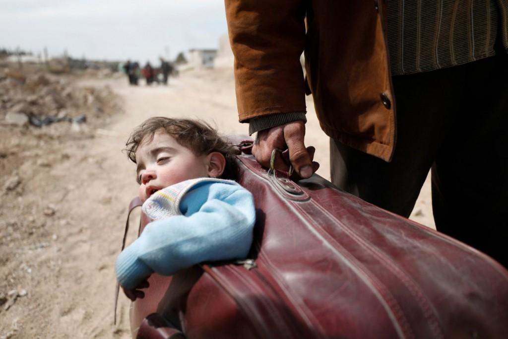 Omar Sanadiki برای UN OCHA. «مردی فرزندش را در ساک قرار داده و بهسمت حموریه میرود جایی که در آن راه خروج باز شده، غُوطَه، سوریه»، مارس 2018