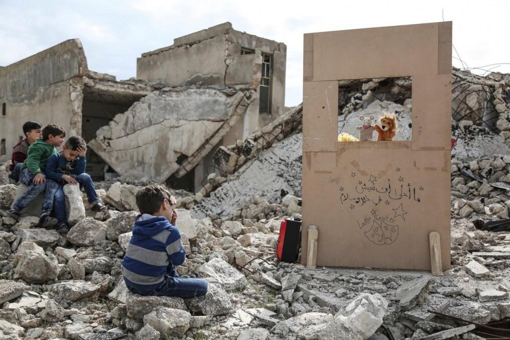 Anas Alkharboutli. «در میان آوار، عروسکگردان ولید راشد برای کودکان اجرای عروسکی میکند، سراقب، سوریه»، مارس 2019