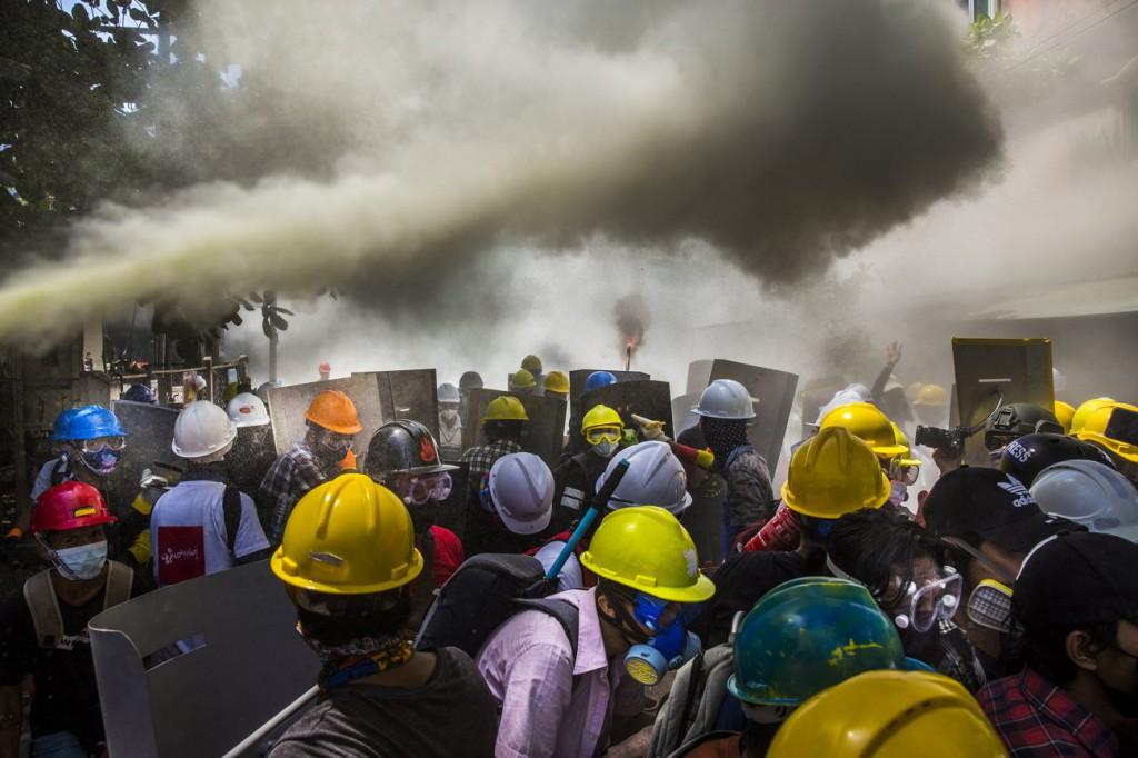 عکاس ناشناس برای نیویورکتایمز. «تظاهرکنندگان جوان ضد-کودتا در مقابل گاز اشکآور و نارنجک صوتی و گلولههای پلاستیکی نیروهای نظامی از کپسول آتشنشانی استفاده میکنند، یانگون، میانمار»، 7 مارس 2021