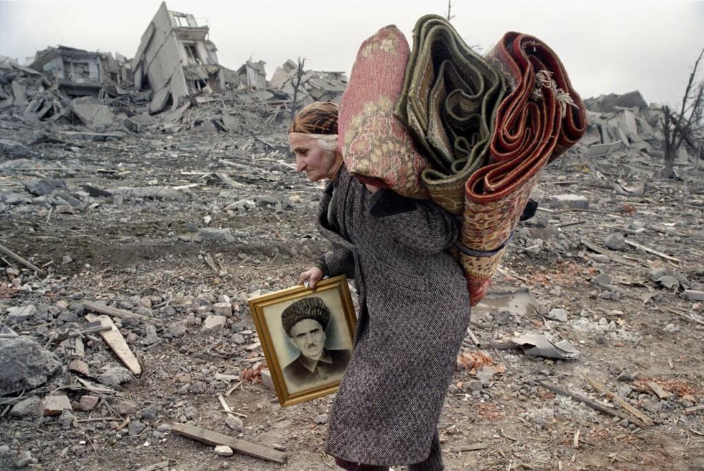 اریک بووه. چچن، فوریه 2000 طی نخستین جنگ چچن (1995 – 1996)، پنج بار به گروزنی رفتم، اما این بار میدان مینوتکا، که نقطهی دسترسی استراتژیکی به پایتخت بود، دیگر قابل تشخیص نبود. همه چیز با خاک یکسان شده بود. تازه رسیده بودم، و این اولین عکسی بود که گرفتم. این زن بهعلت بمباران تمامی ساختمانها از طرف روسها برای جلوگیری از بازگشت جنگجویان چچن و پنهان شدنشان در آنها، مجبور به فرار شده بود. شوهر او و دو پسرش از دنیا رفته بودند. تمام چیزی که با خود داشت چند تکه فرش و عکسی از شوهرش بود.