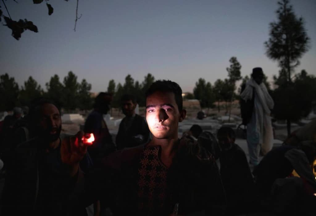 یلدا معیری. مرد جوانی که مواد مخدر مصرف میکند برای اینکه چهرهاش مشخص باشد و من بتوانم از او عکس بگیرم نور را به سمت صورت خود گرفته است. او و بسیاری از معتادان دیگر در یک قبرستان قدیمی در شهر هرات زندگی میکنند.
